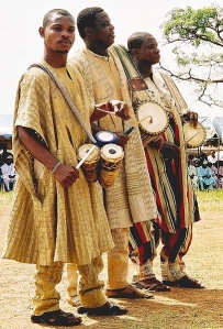 Yoruba drummers: The nearest holds omele ako and batá, the other two hold dunduns.